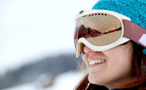 girl smiling in ski goggles at a resort