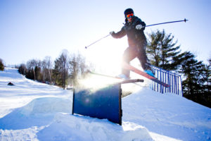 skier riding rails in the sunshine